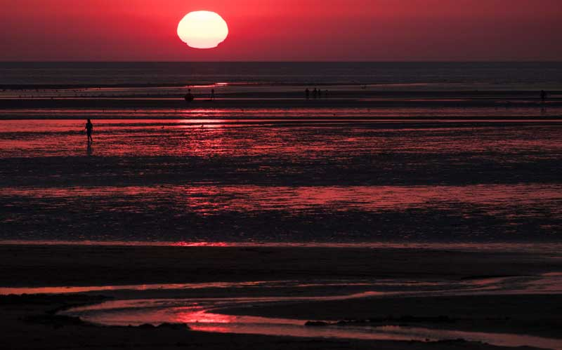 France : People walk on a beach at sunset in Houlgate, northern France, on August 8, 2020. AFP PHOTO