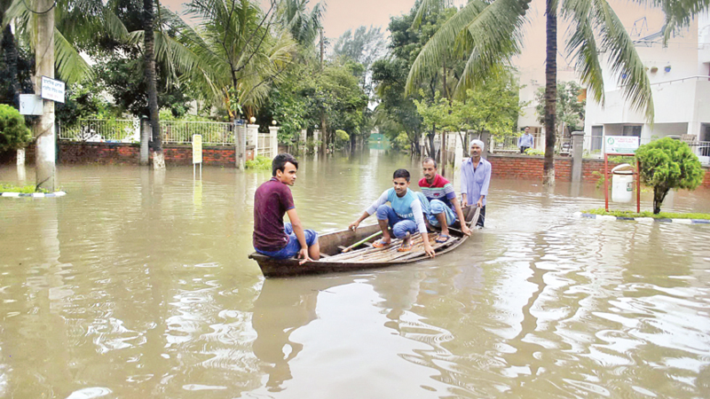 Sudden bursts of rain flood streets of Dhaka, suburbs