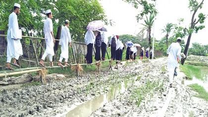 Villagers build bamboo bridge over muddy road