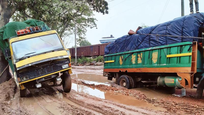 Vehicles ply damaged road amid risk